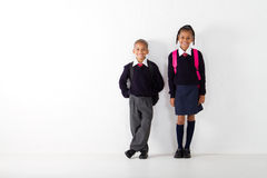 Primary students. Two primary students standing against classroom wall Royalty Free Stock Image