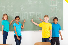 Primary students chinese. Beautiful primary school students pointing their chinese writing work on blackboard stock image