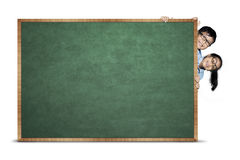 Primary students hiding behind chalkboard. Image of primary students hiding behind blank chalkboard, isolated on white background Royalty Free Stock Photo