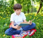 Primavera al aire libre del libro de lectura del muchacho del preadolescente Imagenes de archivo
