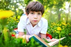 Primavera al aire libre del libro de lectura del muchacho del preadolescente Imágenes de archivo libres de regalías