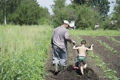 In primavera del padre e del figlio che arano la terra nel giardino Fotografie Stock Libere da Diritti