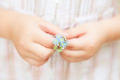 Primavera - fiori di myosotis in mani del ` s del piccolo bambino Fotografia Stock Libera da Diritti