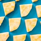 Primavera o concetto di estate: Chiuda sul picchiettio di molti pezzi di ananas giallo che mettono sul fondo di legno blu della t immagine stock
