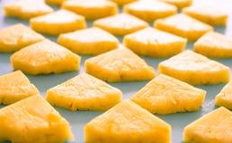 Primavera o concetto di estate: Chiuda sul picchiettio di molti pezzi di ananas giallo che mettono sul fondo di legno blu della t fotografia stock