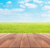 Primavera o estate con il fondo del giacimento del riso ed il piano d'appoggio di legno Fotografia Stock