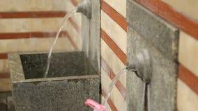Primavera que mana hacia fuera de las facetas incorporadas a las paredes, el tanque de agua plástico debajo de la corriente almacen de metraje de vídeo