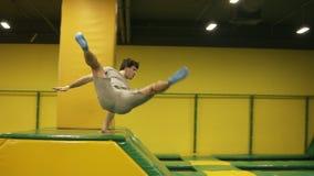 Primaveras masculinas atractivas jovenes de Brunete sobre barrera amarilla en el trampolín profesional Juventud, deporte, gimnasi almacen de metraje de vídeo
