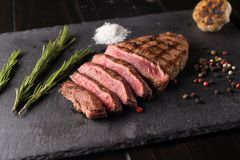 Sliced prime ribeye steak on black stone plate. Medium degree of steak doneness. With rosemary and peppers. Fork and knife. Prime Black Angus Ribeye steak on Royalty Free Stock Image