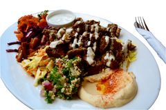 A close-up photo of Lamb shashlik plate, served with traditional fragrant rice, humus, fresh salads and yoghurt mint sauce royalty free stock image