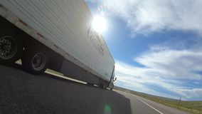 `Prime Inc.` semi-truck pass. `Prime Inc.` Semi Truck passes the viewer to the left on a rural US interstate / motorway stock footage