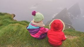 In Prime Position. Children sitting on the edge of a cliff looking out to sea Royalty Free Stock Photo