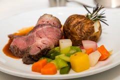Prime Rib mit geschnittenem Gemüse und Ofenkartoffel lizenzfreies stockbild