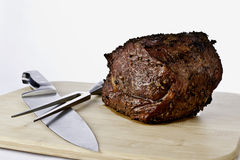 Prime Rib Roast. Sitting on a cutting board with a chef knife and carving fork royalty free stock images
