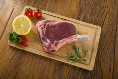 Prime ribs raw on the board. With vegetables Royalty Free Stock Photography