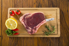 Prime ribs raw on the board. With vegetables Royalty Free Stock Images