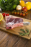 Prime ribs raw on the board. With vegetables Stock Image