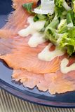 Prime Scottish smoked salmon with salad and dressing. On a blue plate.  Studio image Royalty Free Stock Photography