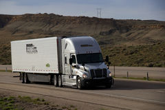 Prime Semi Truck. A White Semi tractor pulls a white PRIME INC trailer along a rural Wyoming interstate Stock Photo