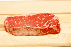 Prime Strip Steak on Wood Cutting Board Stock Photography