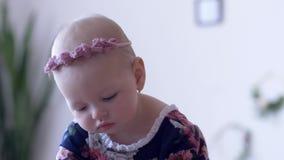 Primeira infância, infante bonito com a decoração elegante na cabeça em fundo unfocused vídeos de arquivo