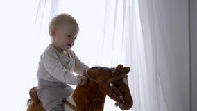 Primeira infância, menino feliz da criança que balança no cavalo do brinquedo em casa filme