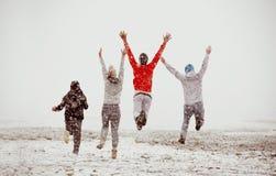 Primeira neve do salto feliz da corrida da amizade dos amigos foto de stock royalty free