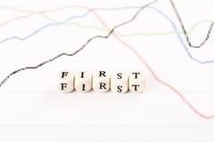 PRIMEIRA palavra escrita com cubos de madeira Imagem de Stock