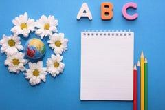 Primeiras letras de ABC- do alfabeto inglês em um fundo azul ao lado do globo pequeno e dos crisântemos brancos Caderno e fotos de stock royalty free