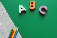Primeiras letras de ABC- do alfabeto inglês em um fundo verde caderno da escola e lápis coloridos Espa?o vazio para o texto foto de stock royalty free