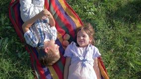 Primeiro amor, crianças que falam e que têm o divertimento na mentira da natureza em uma manta com as maçãs na grama verde filme
