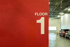 Primeiro andar pintado na parede no estacionamento imagens de stock