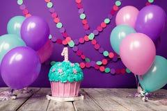 Primeiro bolo de aniversário com uma unidade em um fundo roxo com bolas e a festão de papel fotografia de stock royalty free