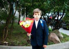 Primeiro dia na escola, menino com flores fotos de stock royalty free