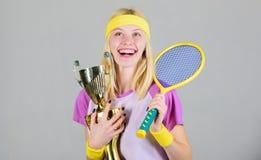 Primeiro lugar Realização do esporte Comemore a vitória Campeão do tênis Raquete de tênis atlética da posse da menina e cálice do fotos de stock