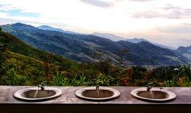 Primeiro plano de aço inoxidável da bacia de lavagem três e montanha bonita no fundo fotos de stock