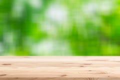 Primeiro plano de madeira com fundo da floresta do verde do borrão fotografia de stock royalty free