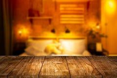 Primeiro plano de madeira com o quarto da noite do borrão para a montagem imagem de stock