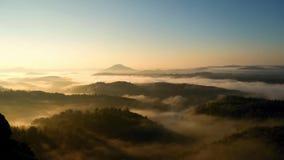 Primeiros raios do sol da aurora fria do outono na paisagem montanhosa Os picos do monte aumentaram do mar nevoento alaranjado e  video estoque