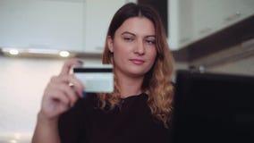 Primer Actividades bancarias en línea hermosas del ` s de las mujeres con una tarjeta de crédito en la tabla con un buen humor HD metrajes