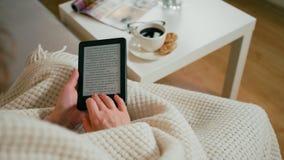 Primer al eBook en e-lector en las manos de la mujer adulta que se sientan en un cuarto acogedor almacen de video