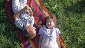 Primer amor, niños que hablan y que se divierten en mentira de la naturaleza en una tela escocesa con las manzanas en hierba verd metrajes