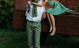 Primer amor no recompensado una muchacha descalza en un vestido verde se sienta en la parte de atrás de un coche y abraza a desca Fotografía de archivo libre de regalías