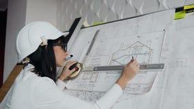 Primer Arquitecto de sexo femenino joven que trabaja en el dispositivo del dibujo un proyecto del modelo del nuevo edificio resid metrajes