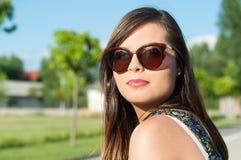 Primer bonito joven de la muchacha que presenta las gafas de sol que llevan Fotos de archivo libres de regalías