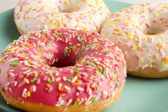 Primer brillante de los anillos de espuma Postre hermoso, adornado Buñuelo apetitoso en helar rosado Fotos de archivo libres de regalías