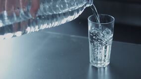 Primer a cámara lenta del batanado de cristal con agua de la botella almacen de metraje de vídeo