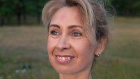 Primer, cara sonriente de una mujer madura en el amanecer almacen de metraje de vídeo