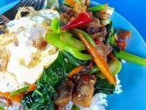 Primer, comida tailandesa: col rizada frita con el huevo curruscante del cerdo Foto de archivo