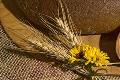 Primer con los cereales, las flores amarillas y el pan. Imagen de archivo